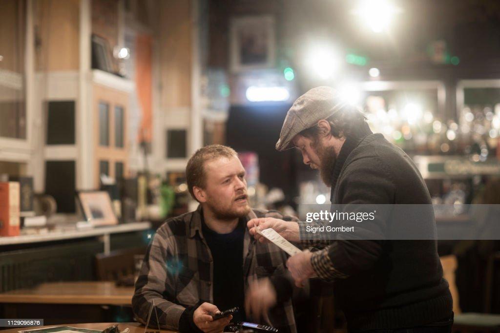Friends paying bill at pub : Stock-Foto