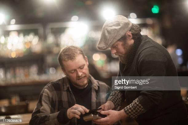 friends paying bill at pub - sigrid gombert stock-fotos und bilder