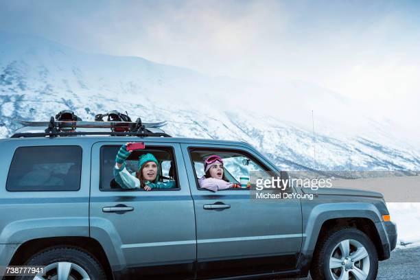 Friends photographing from car in winter