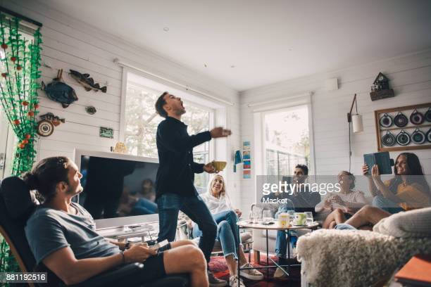 friends photographing man throwing food while standing in living room at home - lanciare foto e immagini stock