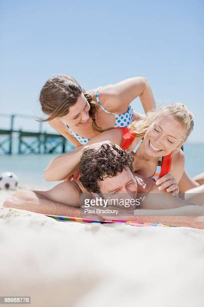 Friends piling on each other at beach