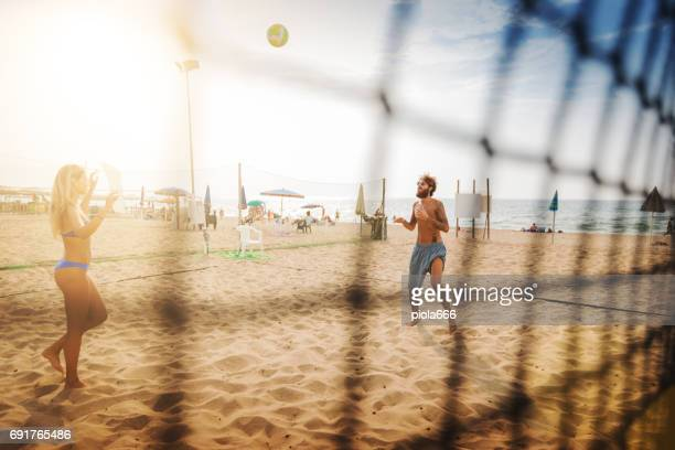 Friends play beach volley and have fun