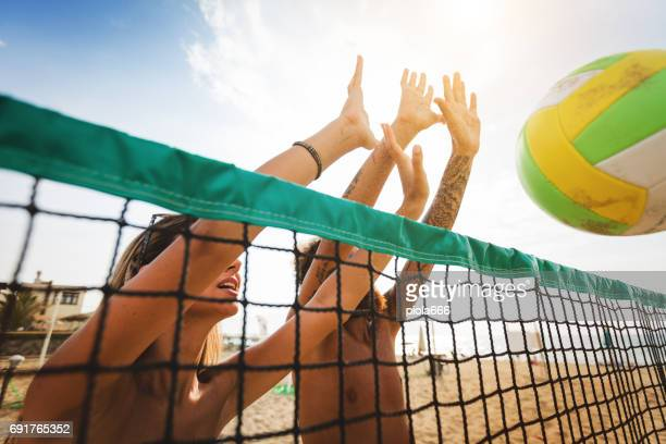 Friends play beach volley: defensive wall