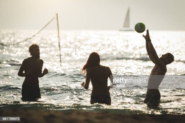 Friends play beach volley in the sea water