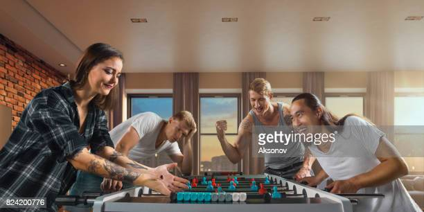 Amis jouent jeu de table football/kicker. Une seule équipe émotionnellement réjouit victoire