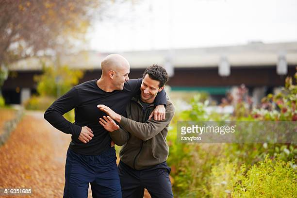 Friends playful while jogging in the park autumn smiling
