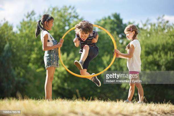 friends playing at park - circle stock pictures, royalty-free photos & images