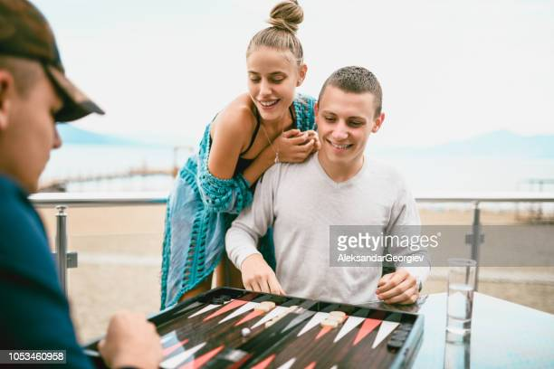 Friends Playing Backgammon At The Beach