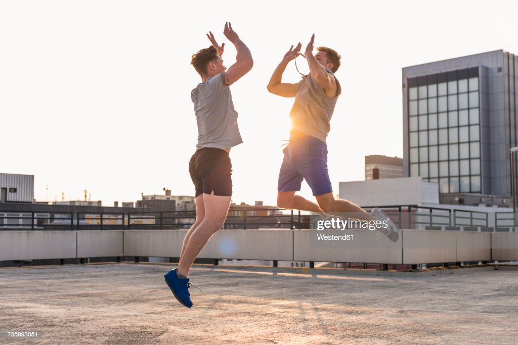 Friends playing basketball at sunset on a rooftop : Stock-Foto