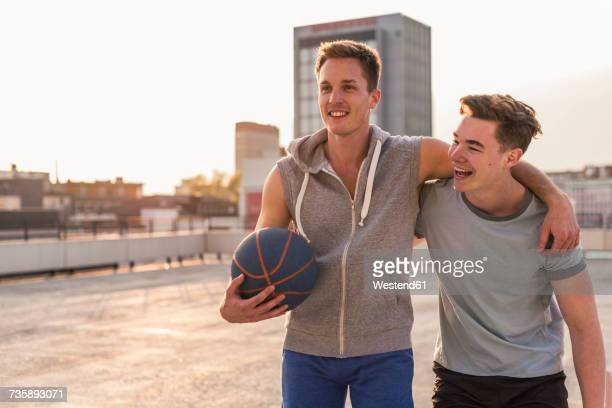 friends playing basketball at sunset on a rooftop - passer le bras autour photos et images de collection