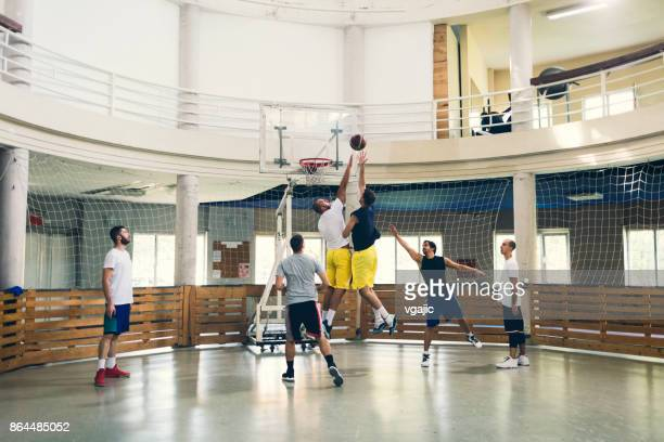 friends playing basketball in a school gym - amateur stock pictures, royalty-free photos & images