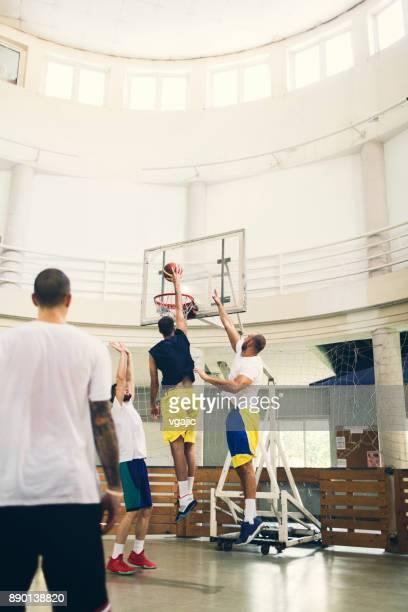 Friends Playing Basketball in a school gym