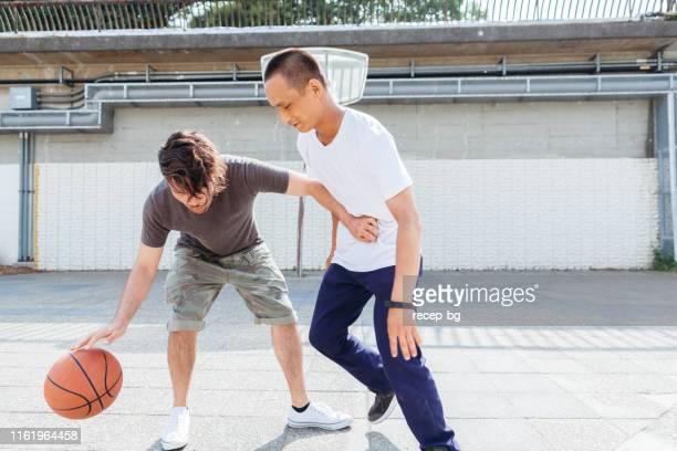 市内でバスケットボールをしている友人 - バスケットボールのシュート ストックフォトと画像