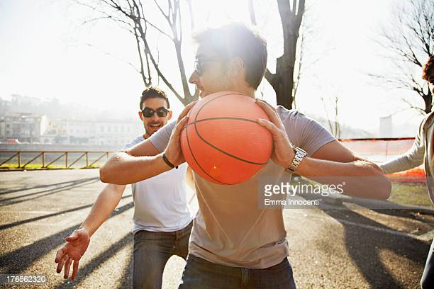 Friends playing basketball in the sun