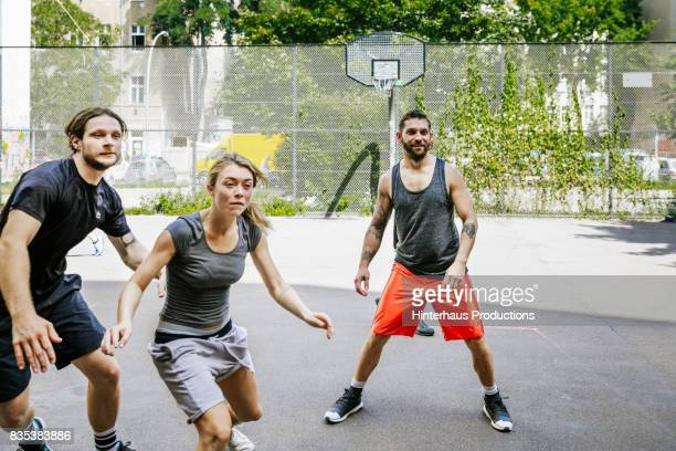Friends Playing Basketball Outdoors Together