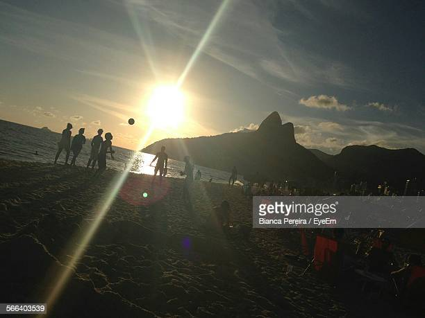 Friends Playing Beach Volleyball Against Sky During Sunset