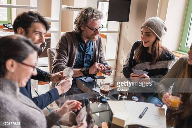 Friends playing cards and games, drinking in modern apartment