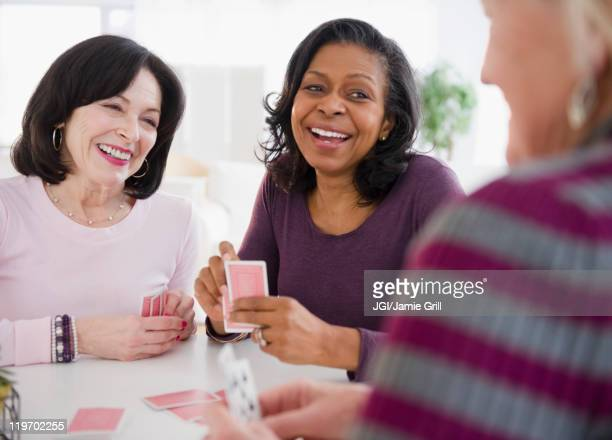 friends playing cards together - poker card game stock photos and pictures