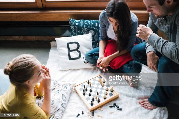 friends playing chess at home on sunny day - game board stock photos and pictures