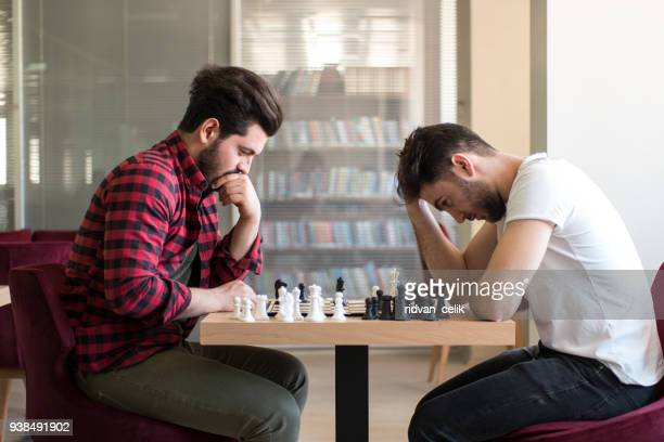 friends playing chess together - chess stock pictures, royalty-free photos & images