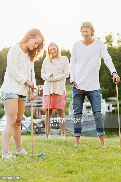 Friends playing croquet on field against clear sky