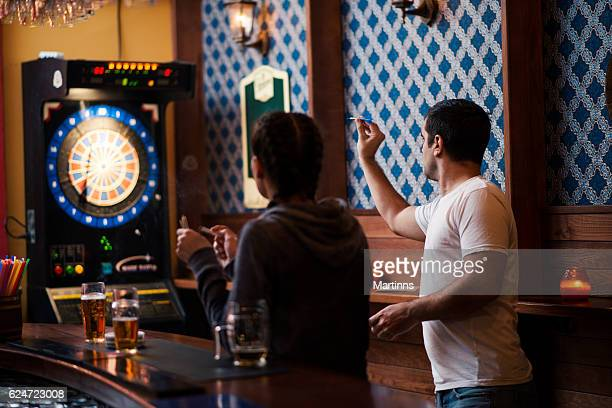 Friends playing darts in a club