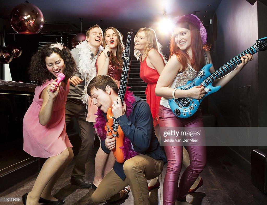 Friends playing fake gitar and singing karaoke. : Stock Photo