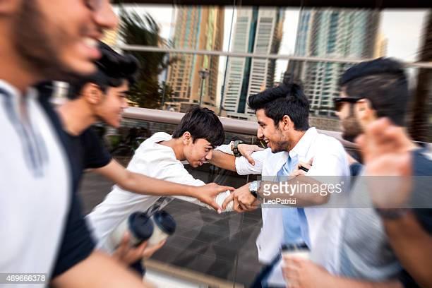 Amigos jugando luchar juntos en la Marina de Dubai