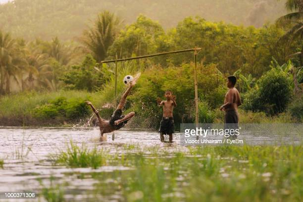 Friends Playing Football In Lake