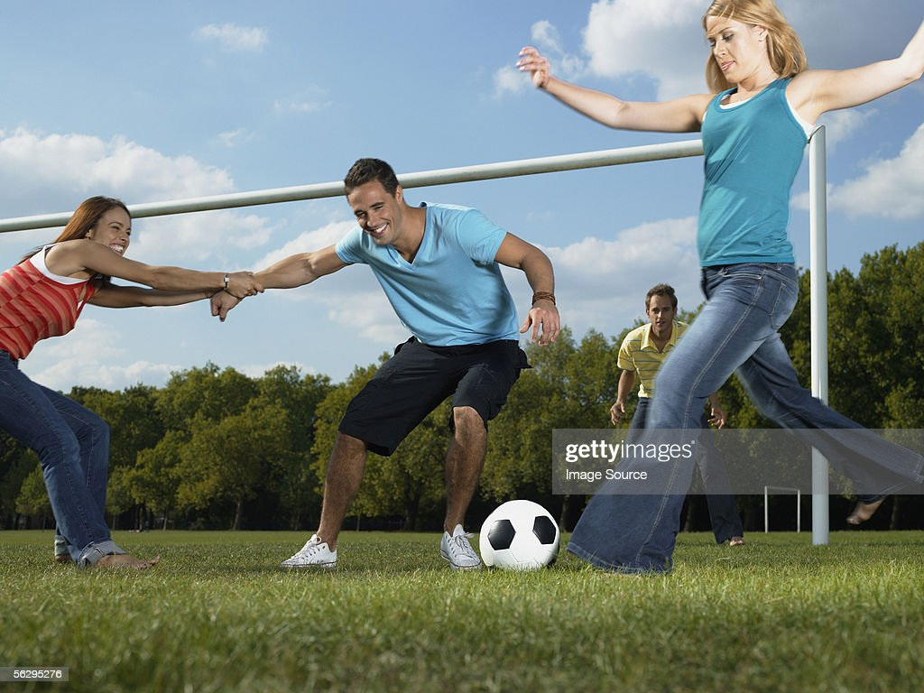 Friends Playing Football In The Park High-Res Stock Photo ...