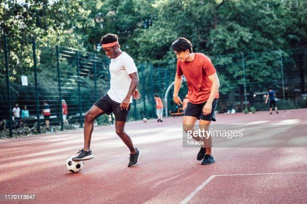 vrienden spelen voetbal - verdediger voetballer stockfoto's en -beelden