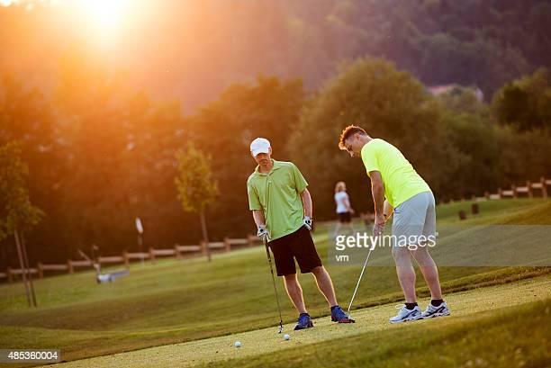 freunde spielen sie golf auf einem oublic golfplatz - einlochen golf stock-fotos und bilder