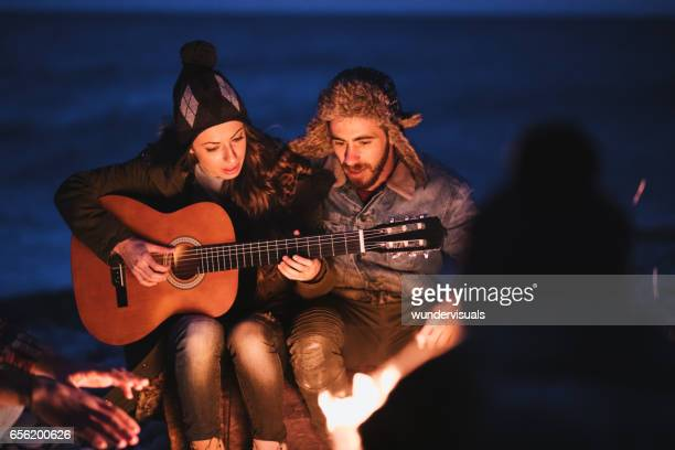 Friends playing guitar and singing at beach party at night