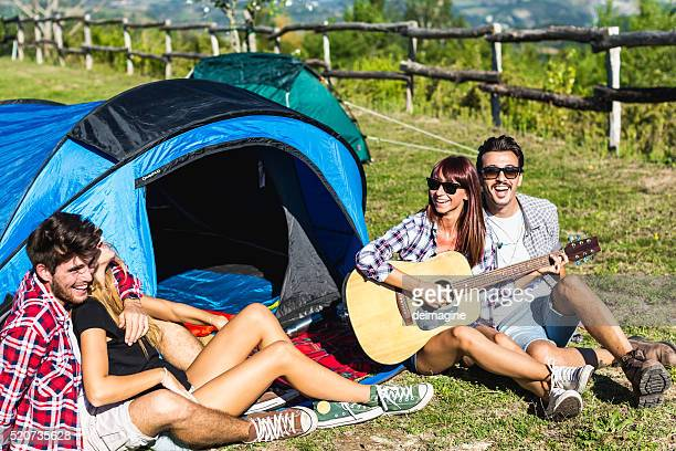 Friends playing guitar near camping tent