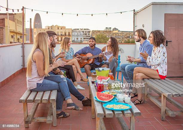 Friends playing guitar on rooftop
