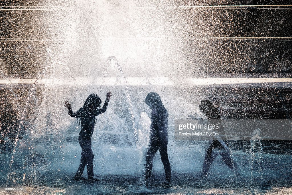 Friends Playing In Fountain : Stock Photo