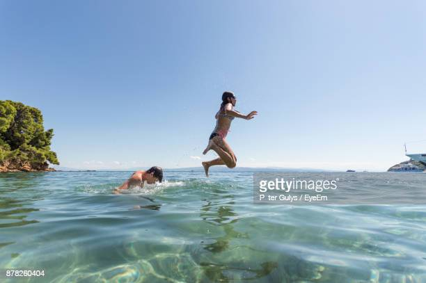 Friends Playing In Sea At Beach
