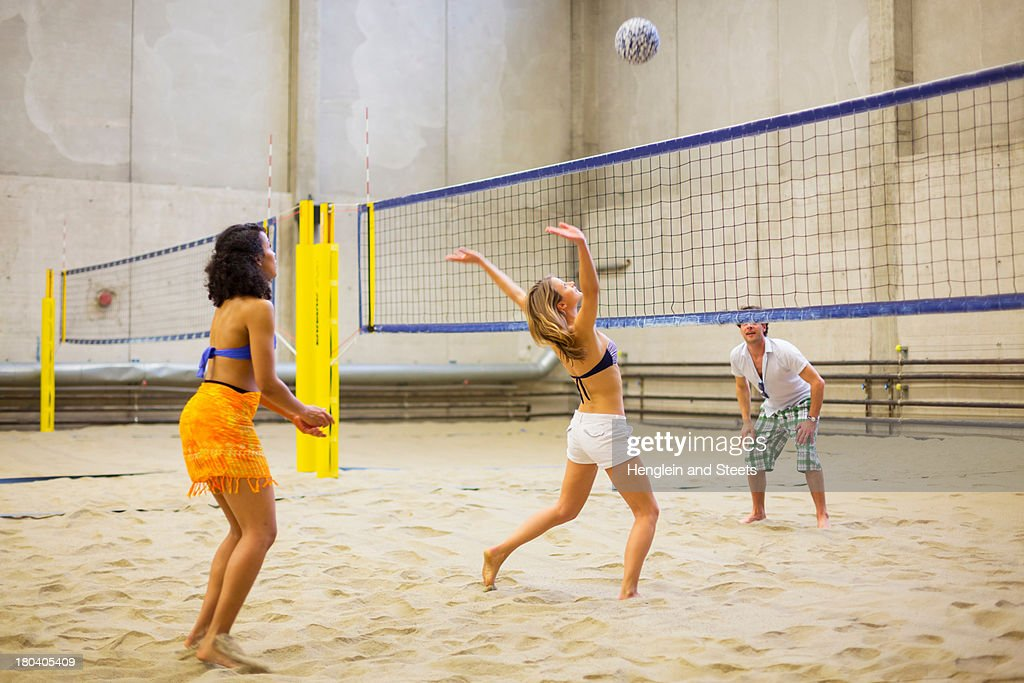 Friends playing indoor beach volleyball : Stock Photo