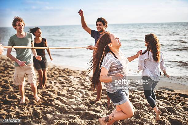 friends playing limbo on the beach
