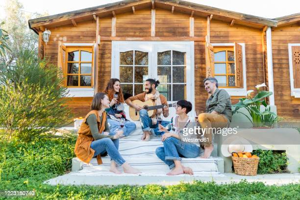 friends playing music on the guitar and drinking wine outside a cabin in the countryside - holiday villa stock pictures, royalty-free photos & images