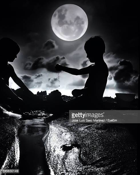 Friends Playing On Beach Against Sky At Night
