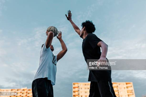 friends playing one on one basketball game - try scoring stock pictures, royalty-free photos & images