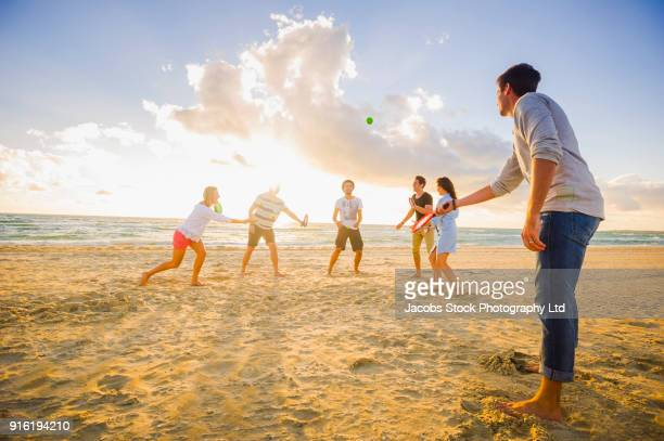 Friends playing paddle ball on beach