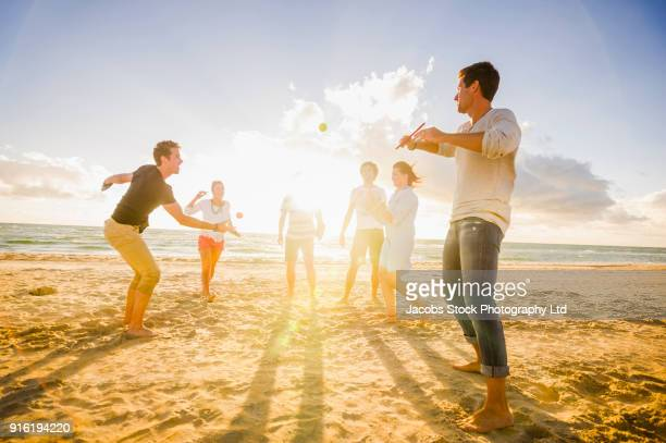 Friends playing paddle ball on sunny beach