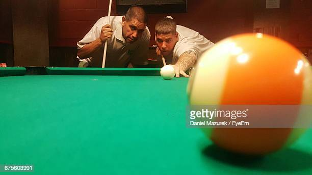 Friends Playing Pool In Hall