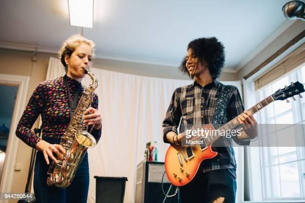 friends playing saxophone and guitar while practicing at recording studio - saxophone stock pictures, royalty-free photos & images