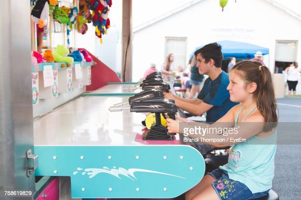 Friends Playing Shooting Game At Carnival