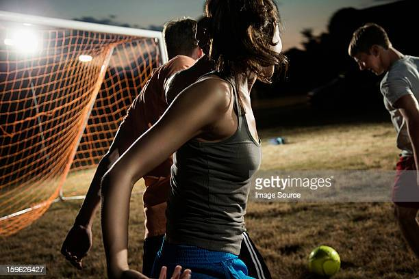 Friends playing soccer at night
