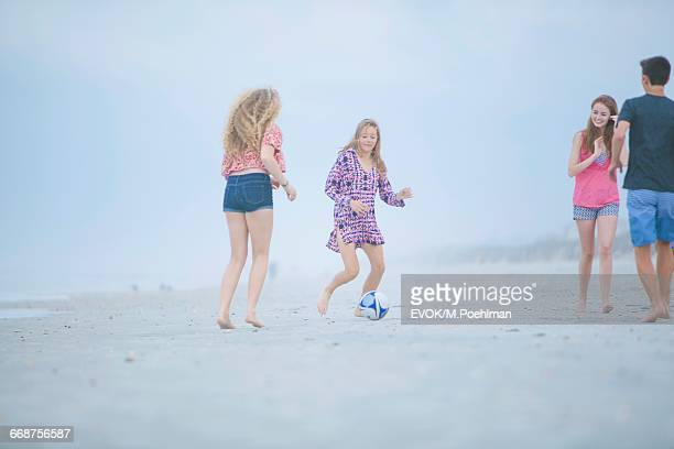 Friends (16-17) playing soccer on beach