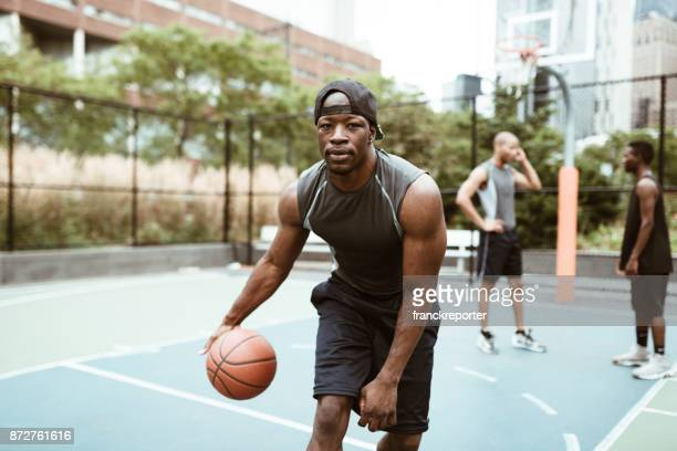 friends playing street basketball in new york city